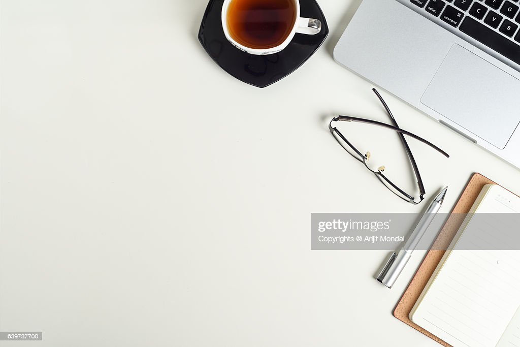 table top background office. office table top view shot with laptop, eyeglass and black tea cup in white background copy space for text u