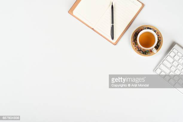 Office table top view with Japanese tea cup plate , pen, computer keyboard and notepad