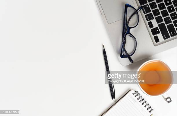 Office table top view with laptop, green tea with cup, eye glasses, pen, notepad copy space