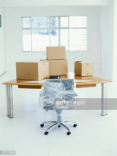 Office table with boxes on it and office chair in wrap.