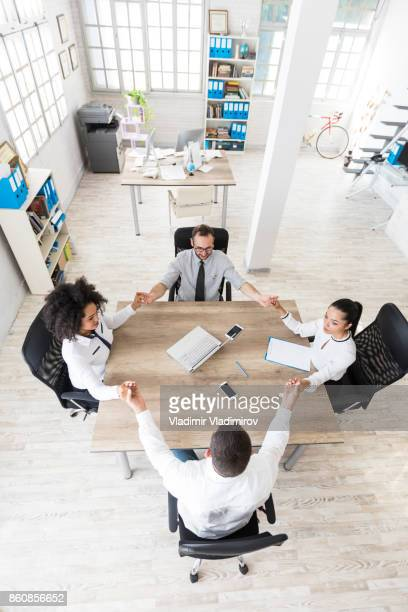 Office team holding hands at work