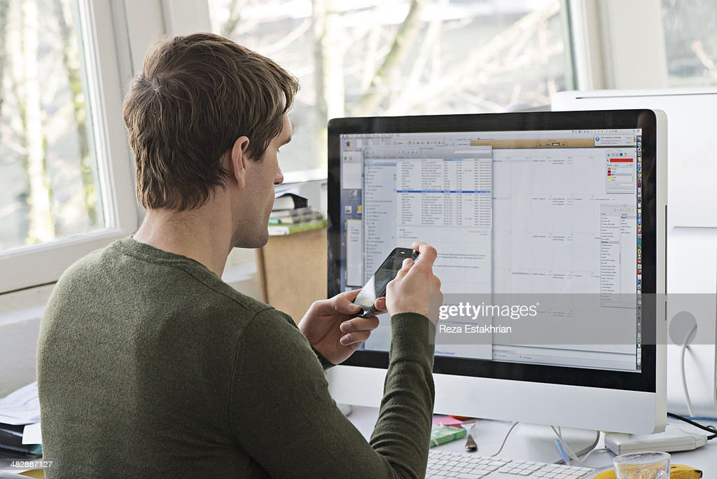 Office worker checks cell phone at work : Stock-Foto