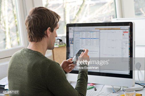 Office worker checks cell phone at work : Stock Photo