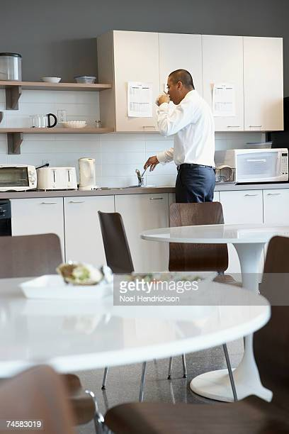 Office worker drinking and reaching for silverware in office lunchroom, rear view