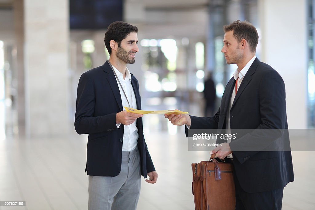 Office worker handing paperwork to businessman in conference centre