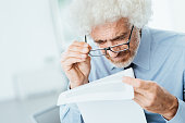 Mature male office worker having eyesight problems while reading paperwork with small text