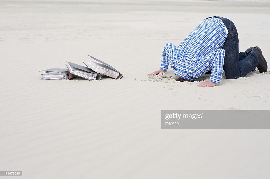 office worker hiding head in sand
