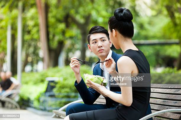 Office Worker Listening To Her Female Colleague During Lunch Outdoors
