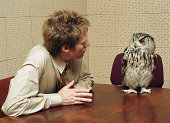 Office worker looking at owl perched on table (Digital Composite)