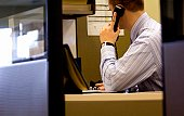 Office worker on phone in cubicle.