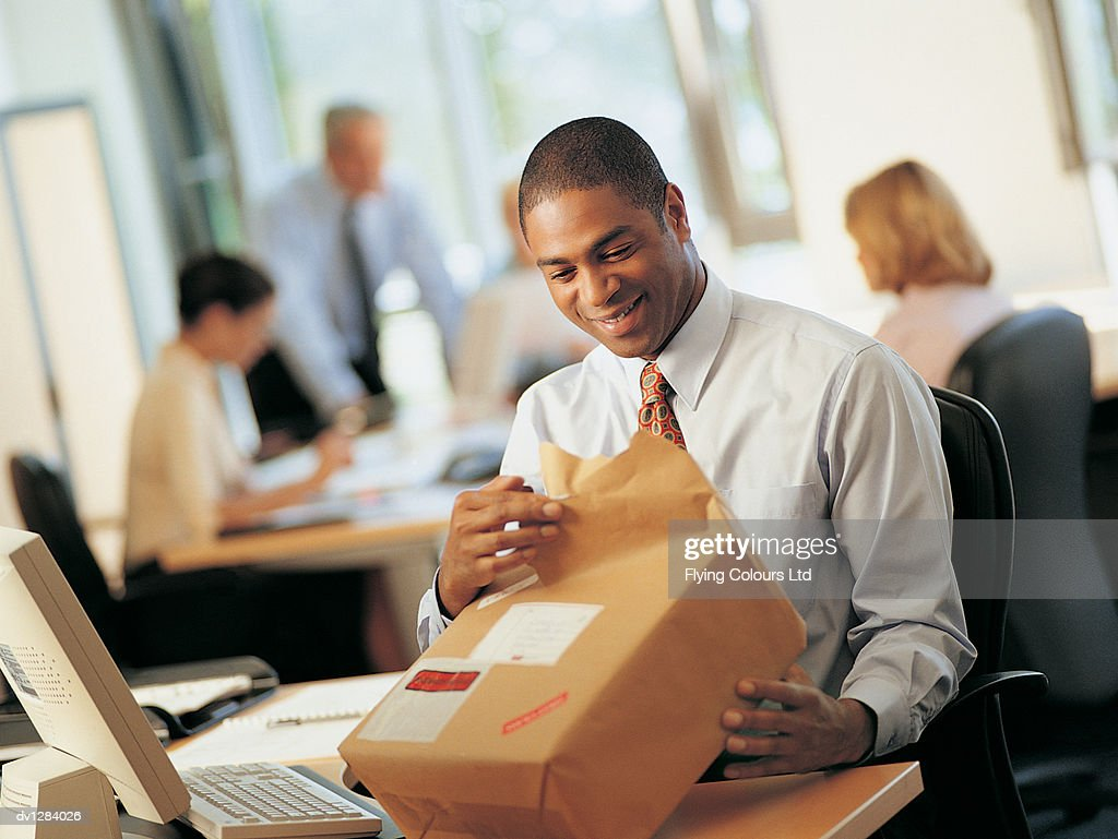 Office Worker Opening a Parcel in a Mailroom : Stock Photo