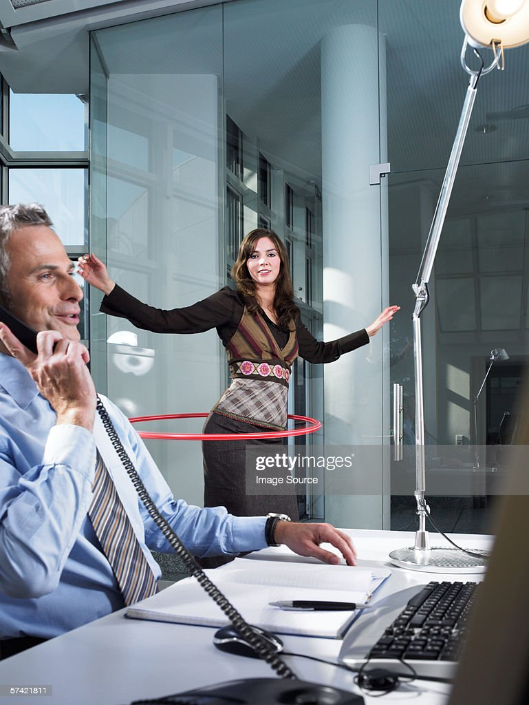 Office worker playing with hula hoop : Stock Photo