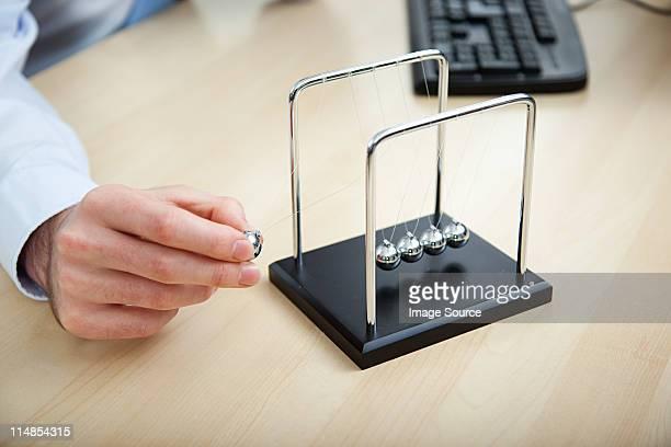 Büroberuf spielt mit newtons cradle