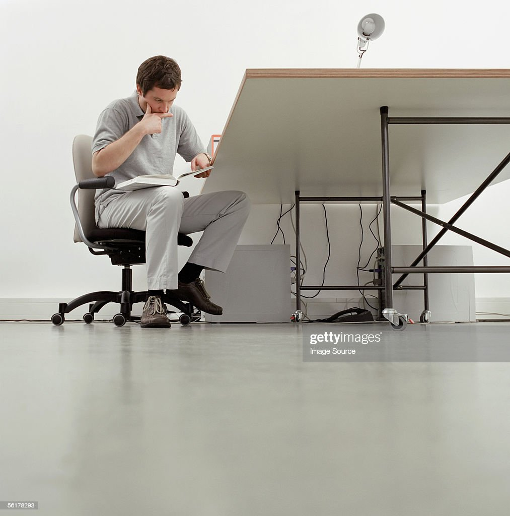 Office worker reading a book : Stock Photo