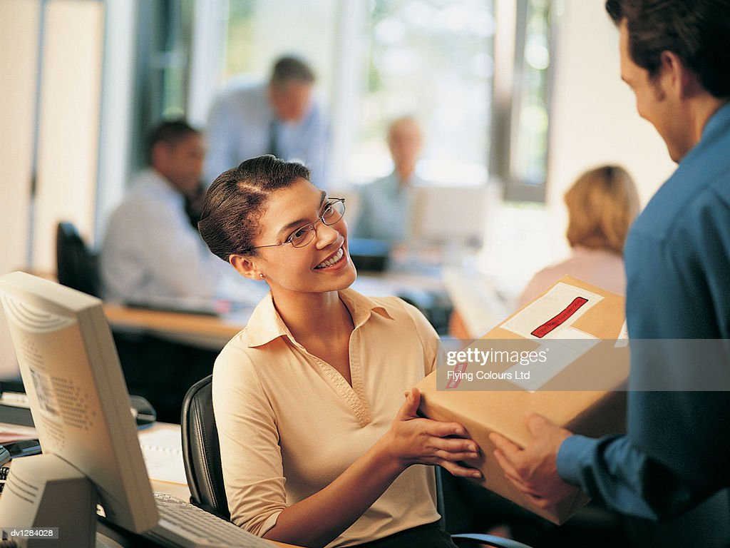 Office Worker Receiving a Parcel From a Colleague in an Office Sorting Room : Stock Photo
