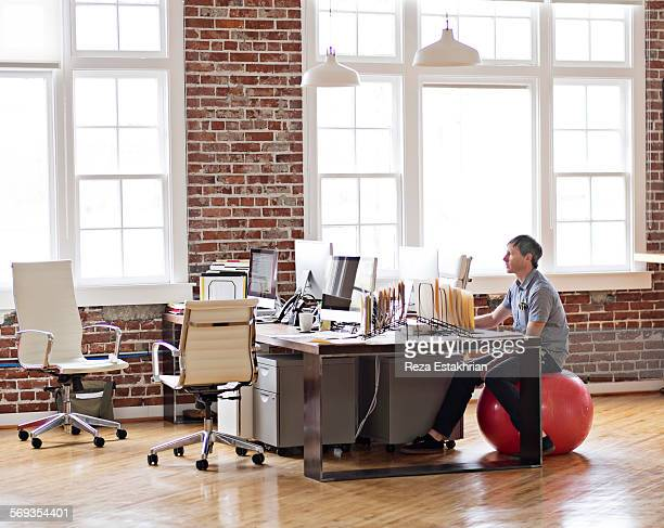 Office worker sits on balance ball at his desk
