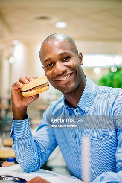 Office worker smiling hamburger in hand