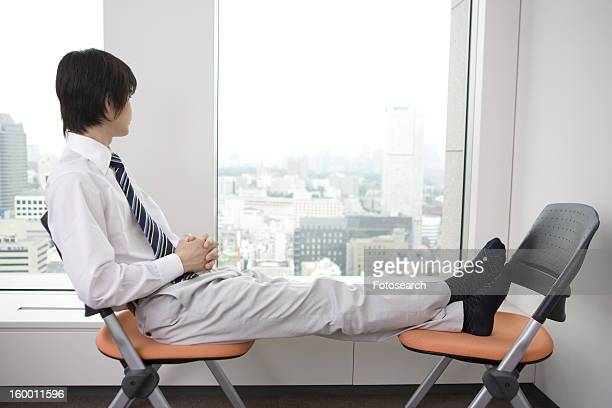 Office worker taking a break with stretching his foot on a chair
