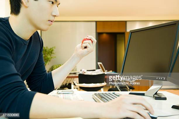 Office worker using computer, squeezing stress ball with one hand
