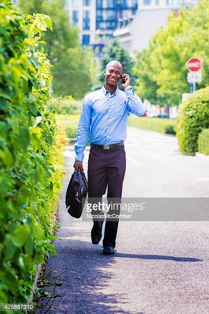 Office worker walking back home phone in hand smiling