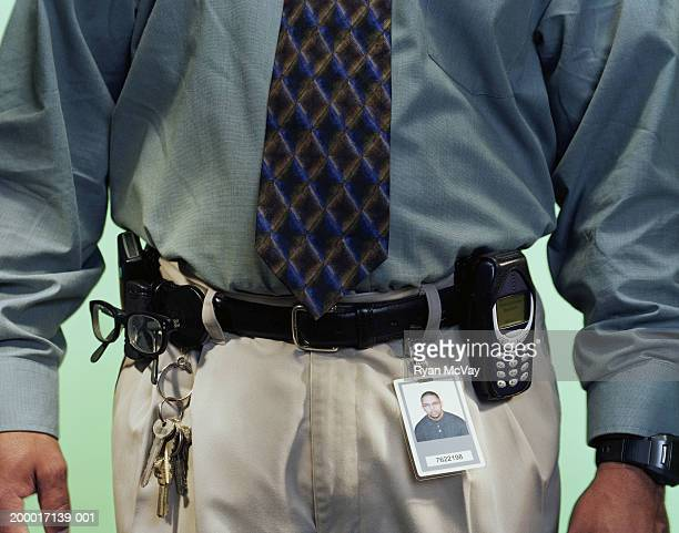 Office worker wearing ID badge on belt, mid section, close-up