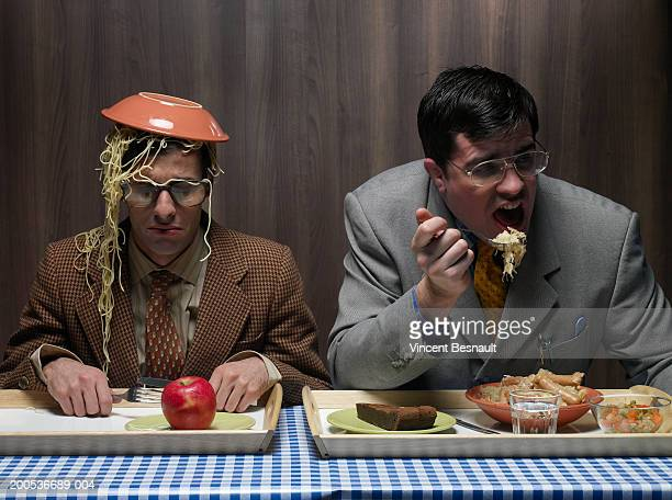 Office worker with bowl of pasta on head next to colleague in canteen