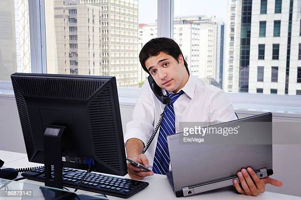 Office worker with multiple computers and phones in office