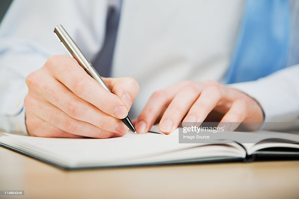 Office worker writing in diary : Stock Photo