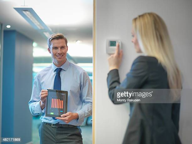 Office workers adjusting heating thermostat and recording information on digital tablet