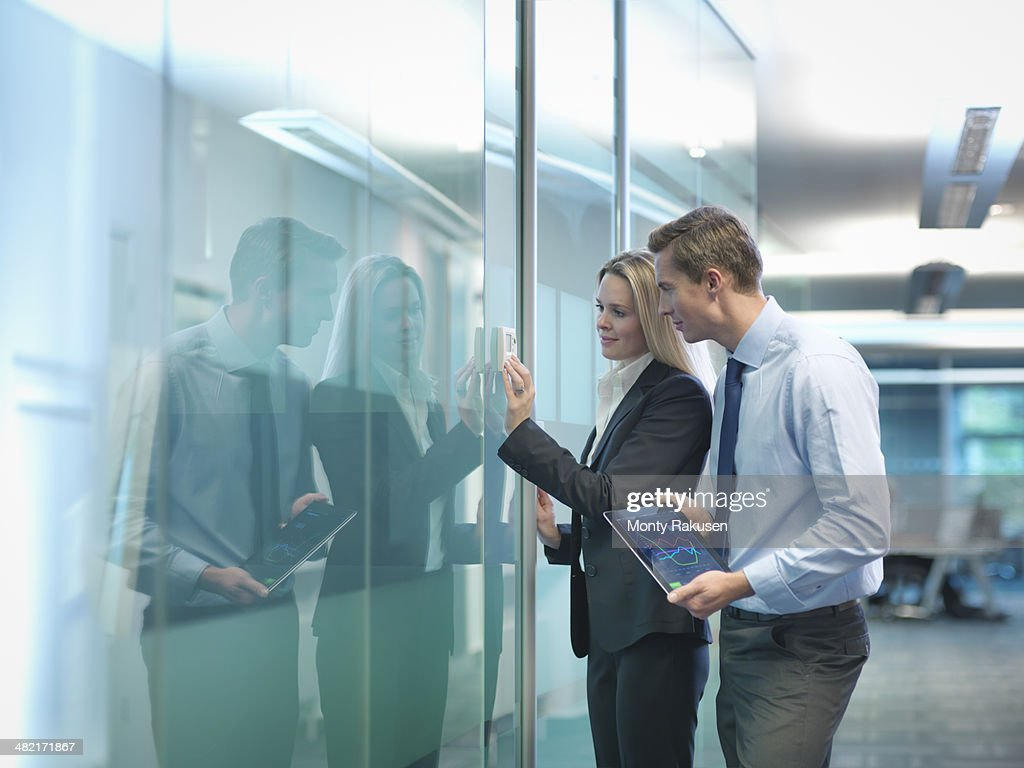 Office workers adjusting heating thermostat in modern workplace