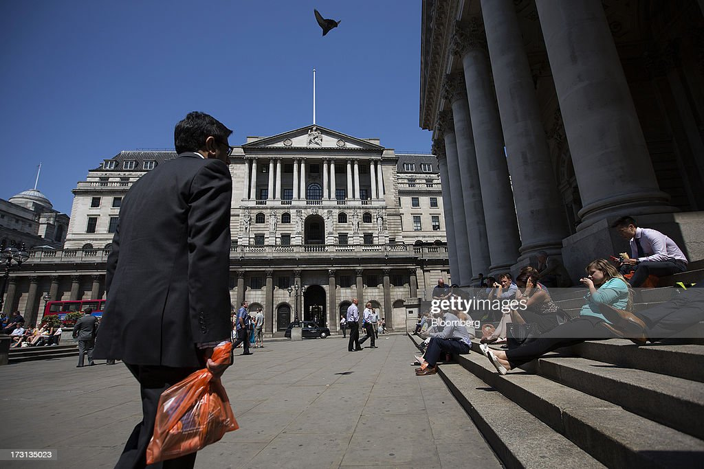 Office workers and tourists sit on the steps of the Royal Exchange, right, near the the Bank of England in London, U.K., on Monday, July 8, 2013. Britain's economy could be in line for a period of 'strong catch-up growth' once it gets through the current weakness, according to Capital Economics Ltd. Photographer: Simon Dawson/Bloomberg via Getty Images