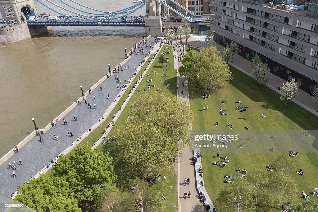 Office workers and visitors sitting in Potters Field public park which is located near the south-west of Tower Bridge in London, United Kingdom on May 6, 2016.