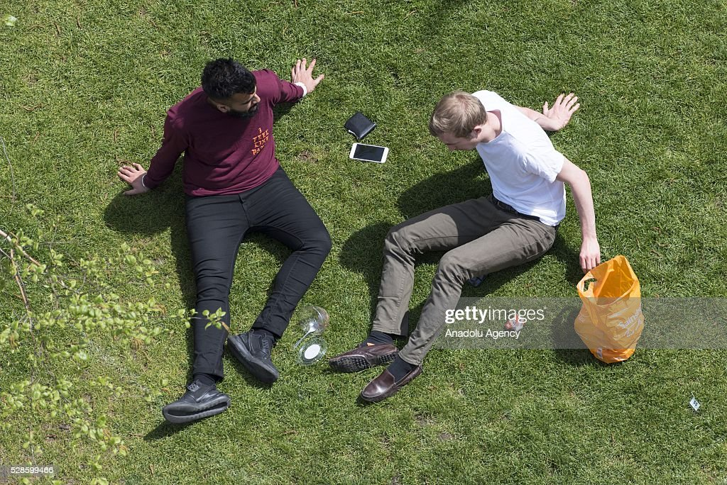 Office workers and visitors sitting in Potters Field public park during lunch hour thenjoying the 23c weather in London, United Kingdom on May 6, 2016.