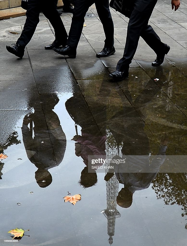 Office workers are reflected in rain water during the lunch hours in the Central Business District of Sydney on April 16, 2013. Australia's central bank said it hadn't ruled out extending a more-than-yearlong rate-lowering cycle as the resource-rich country's economy battled a slowdown in mining investment, a stubbornly strong currency, and steep government spending cuts. AFP PHOTO / Saeed Khan