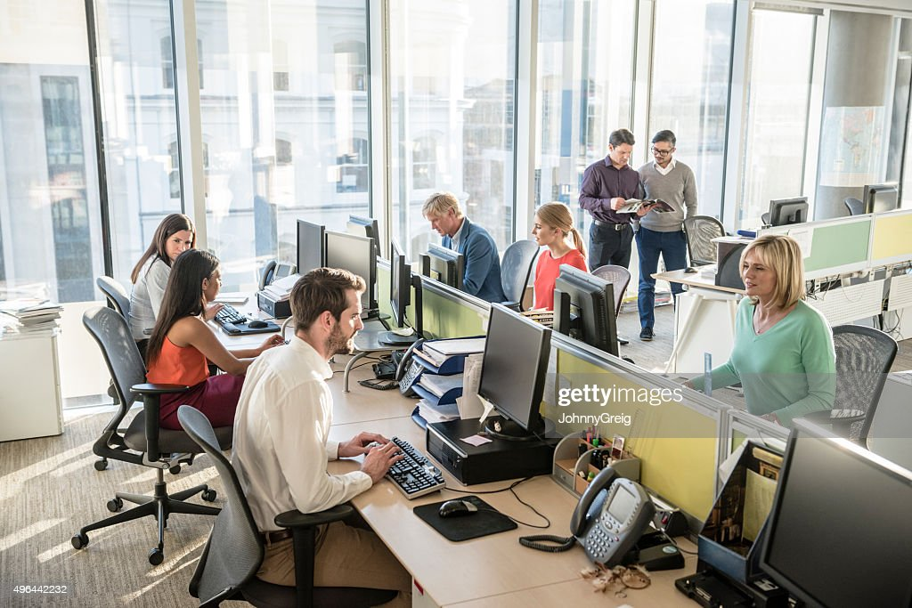 Office workers at desks using computers in modern office : Stock Photo