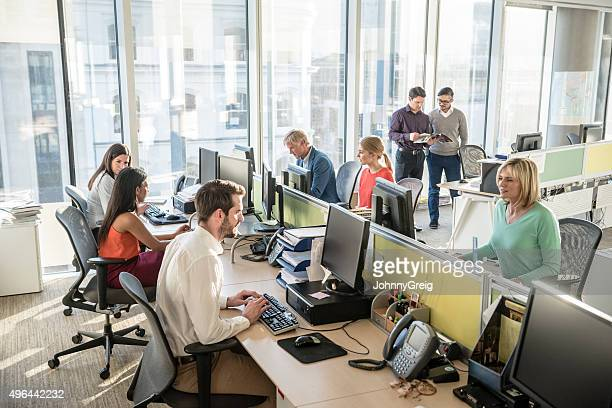 Office workers at desks using computers in modern office
