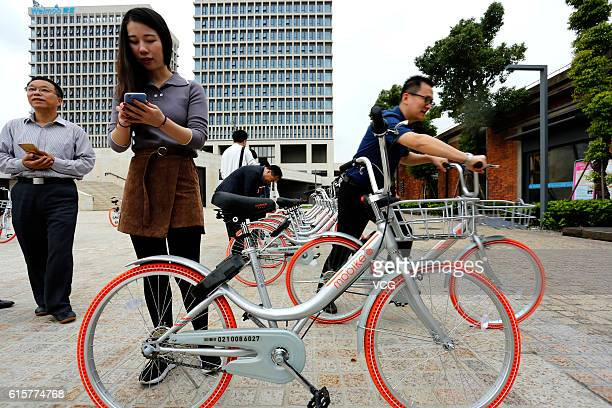 Office workers experience the Mobike Lite bicybles at Baoshan District on October 19 2016 in Shanghai China The bikesharing service company Mobike...