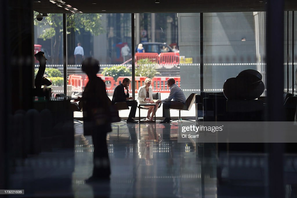 Office workers hold a meeting the lobby of a skyscraper in the City of London on July 10, 2013 in London, England.