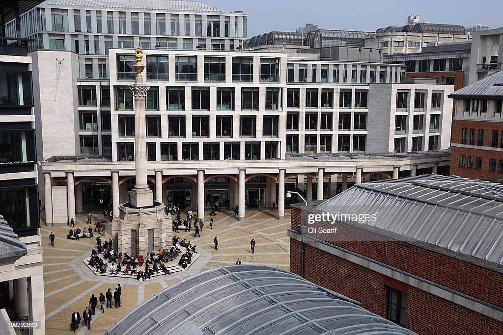 Office workers sit around a monument in Paternoster Square, in front of the London Stock Exchange, at lunchtime on April 10, 2013 in London, England.