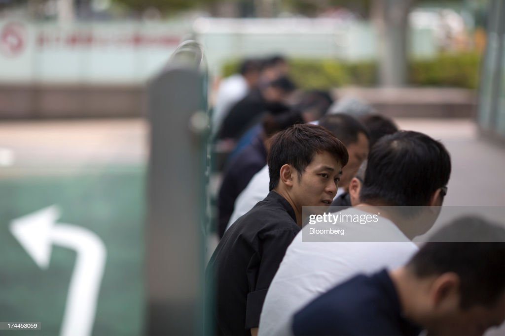 Office workers sit in a smoking area outside the Taipei 101 building in Taipei, Taiwan, on Wednesday, July 24, 2013. Taiwan President Ma Ying-jeou ruled out driving down the Taiwan dollar to boost exports following the currencys rally against the yen and said the government still aims for growth of at least 2 percent this year. Photographer: Jerome Favre/Bloomberg via Getty Images