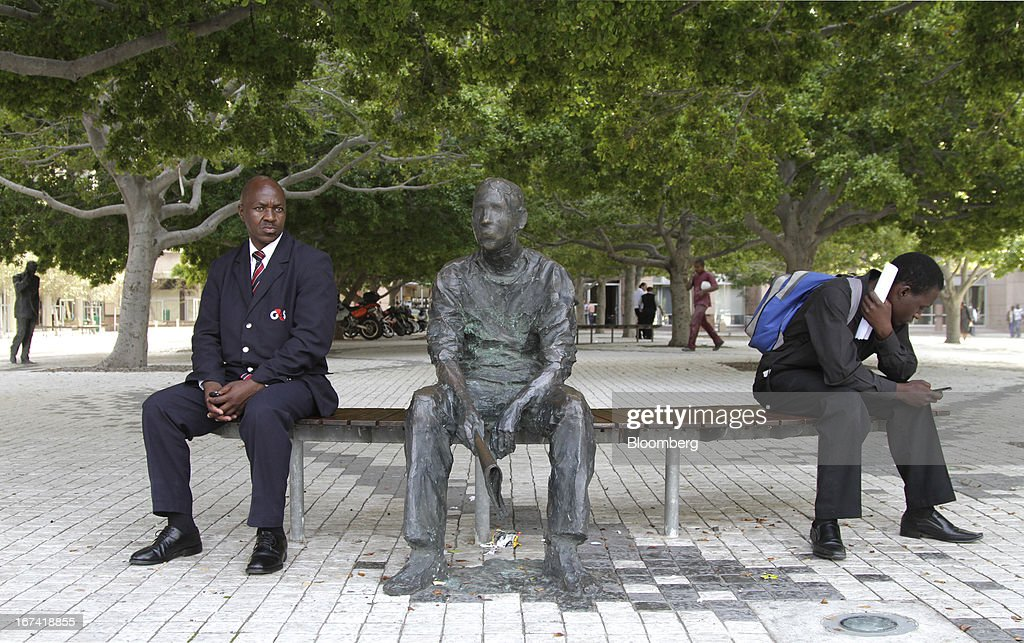 Office workers sit on a public bench in the city center in Cape Town, South Africa, on Wednesday, April 24, 2013. South Africa's gross domestic product is forecast to expand 2.6 percent this year, compared with 2.5 percent in 2012, according to the country's central bank. Photographer: Nadine Hutton/Bloomberg via Getty Images