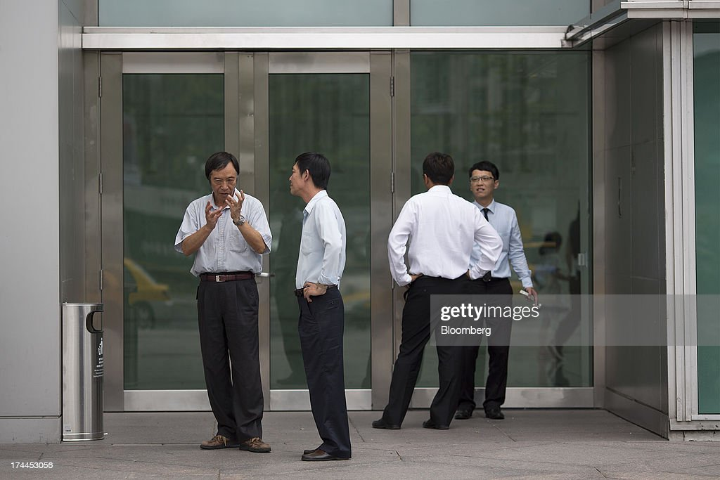 Office workers smoke cigarettes in a smoking area outside the Taipei 101 building in Taipei, Taiwan, on Wednesday, July 24, 2013. Taiwan President Ma Ying-jeou ruled out driving down the Taiwan dollar to boost exports following the currencys rally against the yen and said the government still aims for growth of at least 2 percent this year. Photographer: Jerome Favre/Bloomberg via Getty Images