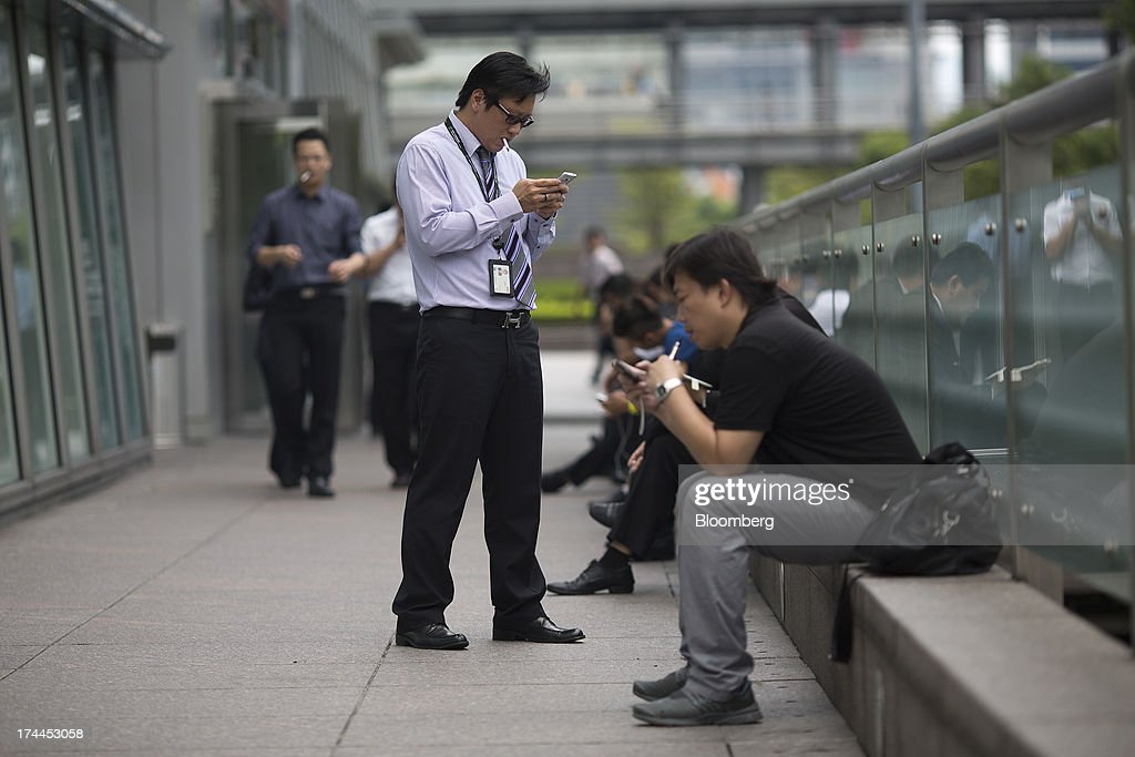 Office workers smoke cigarettes while using mobile devices in a smoking area outside the Taipei 101 building in Taipei, Taiwan, on Wednesday, July 24, 2013. Taiwan President Ma Ying-jeou ruled out driving down the Taiwan dollar to boost exports following the currencys rally against the yen and said the government still aims for growth of at least 2 percent this year. Photographer: Jerome Favre/Bloomberg via Getty Images