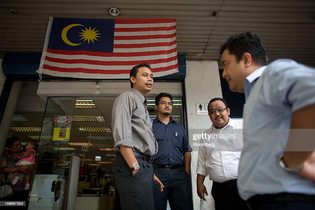 Office workers stand in front of a flag of Malaysia displayed outside a supermarket during lunch hour in the central business district in Kuala Lumpur, Malaysia, on Wednesday, Jan. 16, 2013. While many developed countries have faltered, Malaysia's gross domestic product growth has exceeded 5 percent for five quarters with domestic demand countering a slowdown in exports. Photographer: Lam Yik Fei/Bloomberg via Getty Images