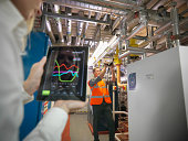 Office workers using digital tablet and camera to check efficiency of office heating in boiler room