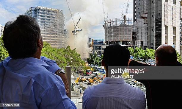 Office workers watch as water is sprayed on the site of a fire at the Barangaroo construction site which threw plumes of smoke over Sydney's central...