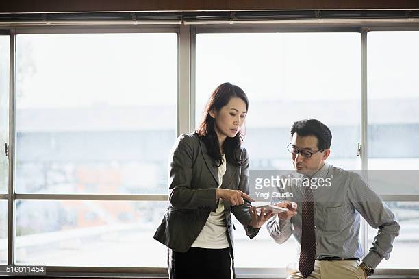 Office workers working together on tablet pc
