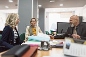office workes talking and looking files: women and mature boss at desk. Real enviroment