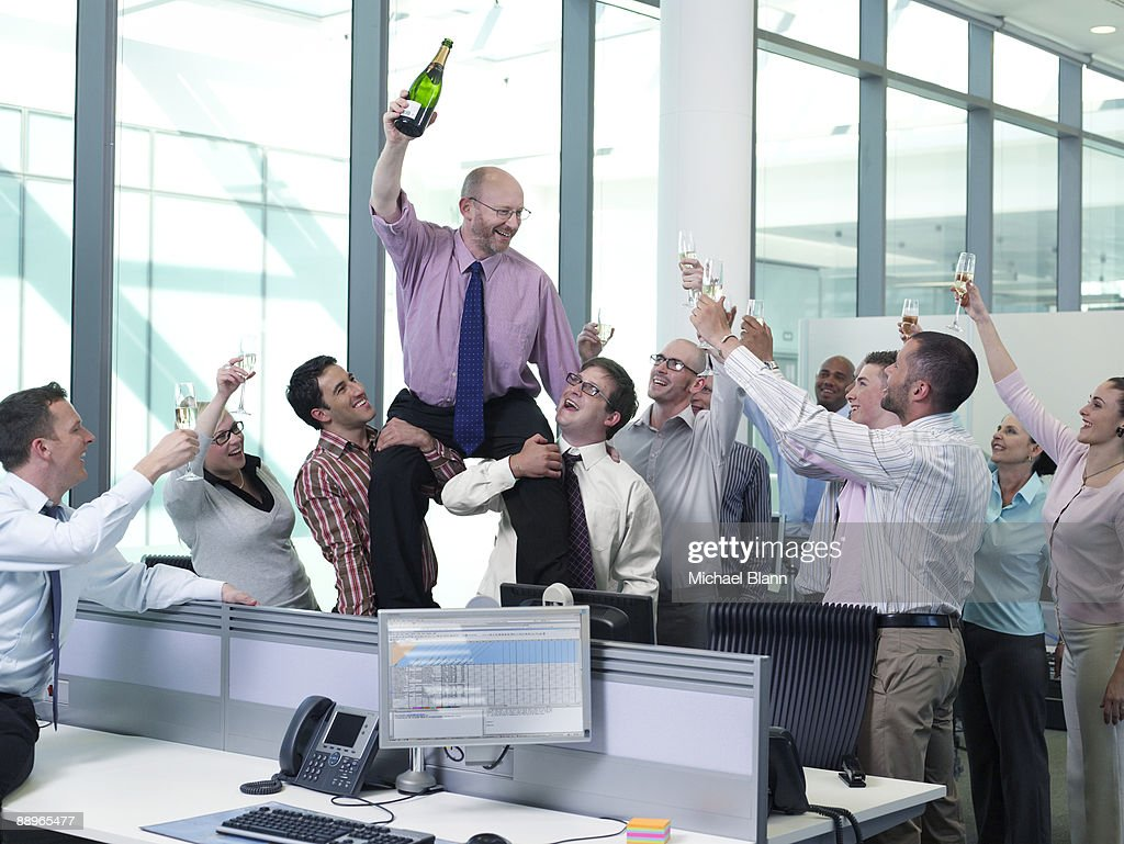 officemates giving toast of champagne to the boss