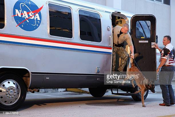 K9 officer and his dog exit the Astrovan before the crew of space shuttle Atlantis STS135 take the vehicle to the launch pad hours before their...